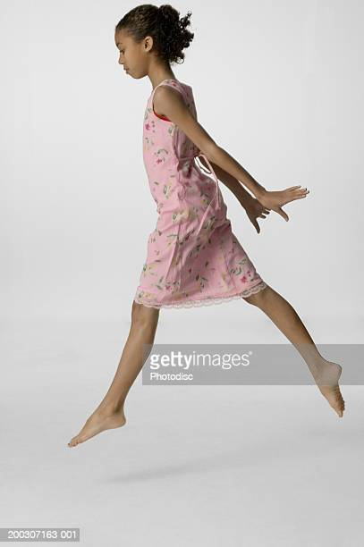 Young girl (12-13), with dark hair, skipping in studio, portrait