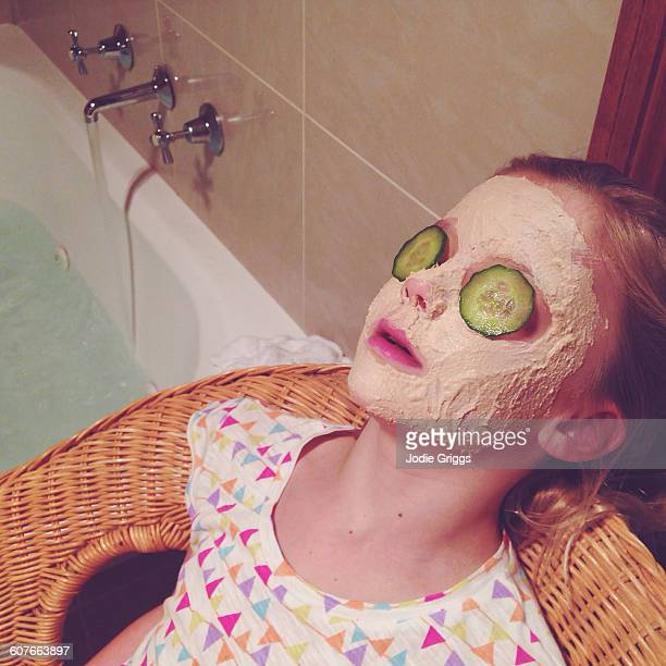 Young girl with face mask and cucumber on eyes