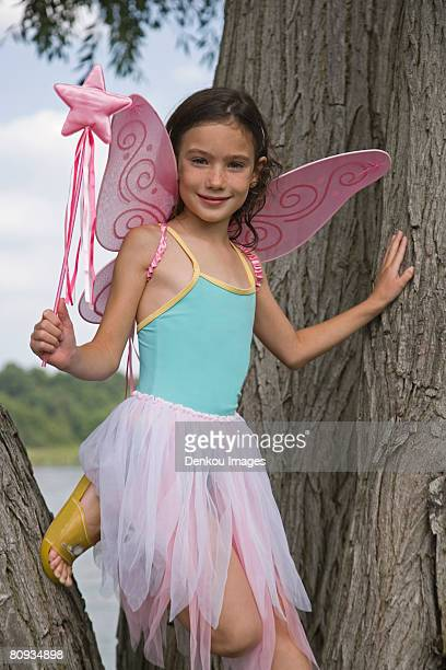 Young girl with fairy wings and wand standing in tree