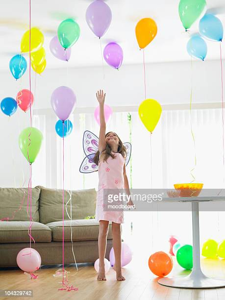 Young girl (7-9) with fairy wings reaching for balloon in living room