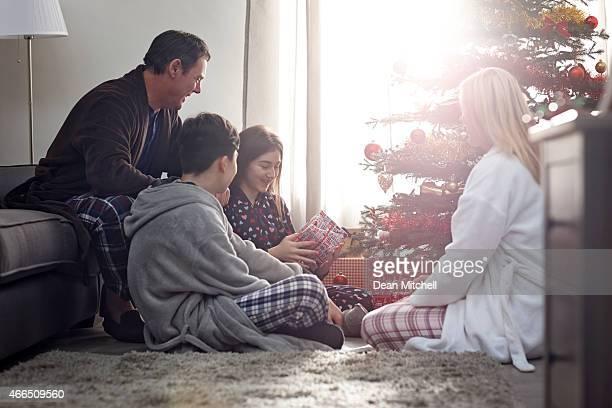 Jeune fille avec la famille se son cadeau de Noël au matin
