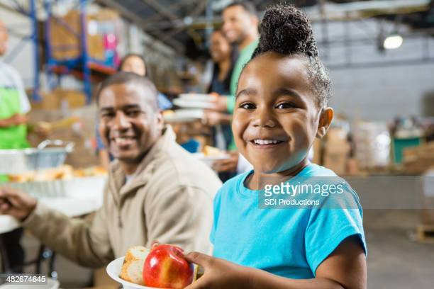 Young girl with father eating healthy food at soup kitchen