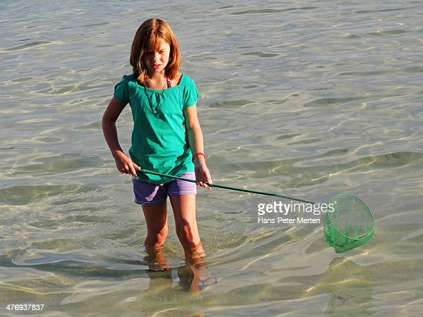 young girl with fishnet on the beach