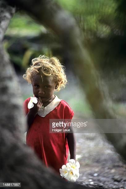 Young girl with frangipani flowers, Busu Village.