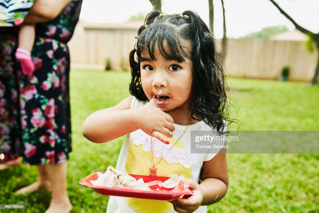 Young girl with frosting on face eating cake during family birthday party : Stock Photo