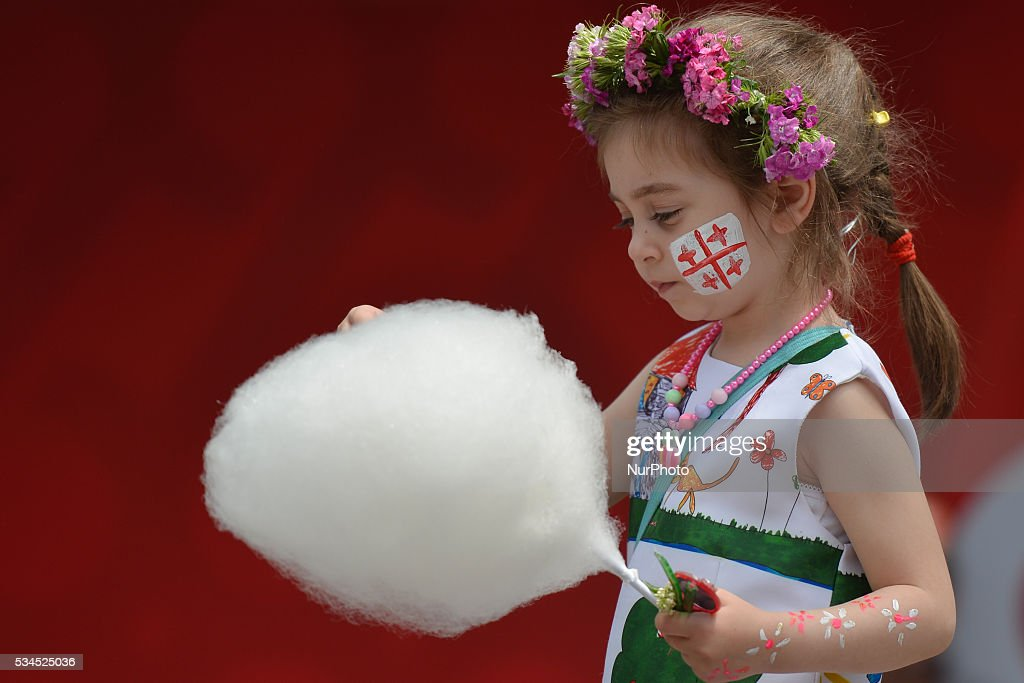 A young girl with Georgian flag paintings on her face enjoys a cotton candy, as many people of all age gathered in Tbilisi center for a popular celebrations. Today, Georgia Celebrates its Independence Day commemorating the adoption of the Act of Independence in 1918, that outlined the main principles of the nation's democratic development and formed a first-ever republic under German and British protection, but was then invaded by Bolshevik Russia and absorbed into the Soviet Union. On April 9, 1991, Georgia once again regained its independence. This year Georgia celebrates the 25th Anniversary since the restoration of its independence. Tbilisi, Georgia, on Thursday 26 May 2016.