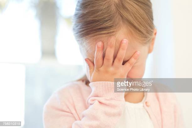Young girl with hand on face