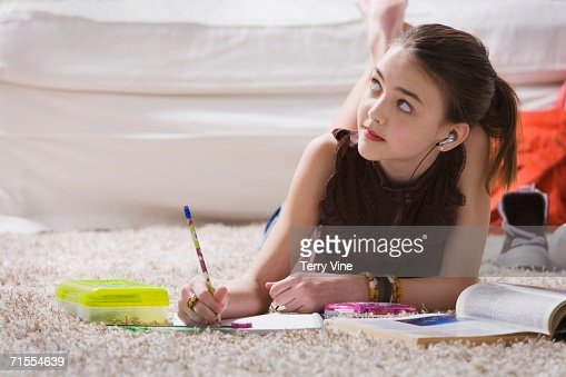 Young girl with headset doing homework on floor : Foto de stock