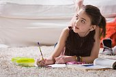 Young girl with headset doing homework on floor