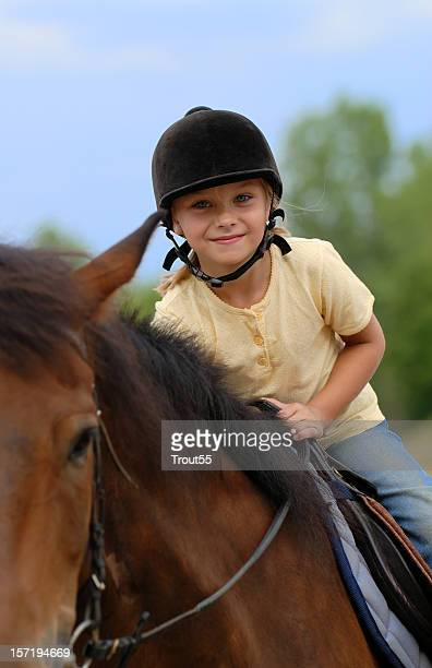 Young girl with helmet riding a horse