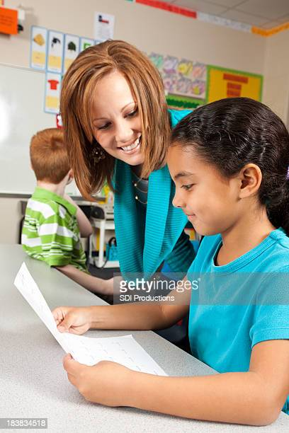 Young Girl With His Teacher Happy About Good Grade