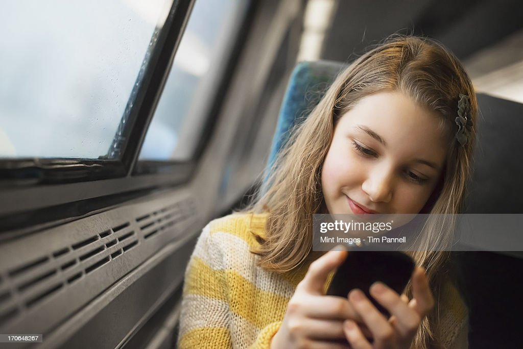 A young girl with long blonde hair sitting by a window on a train, using her mobile phone, texting and sending messages. : Stock Photo