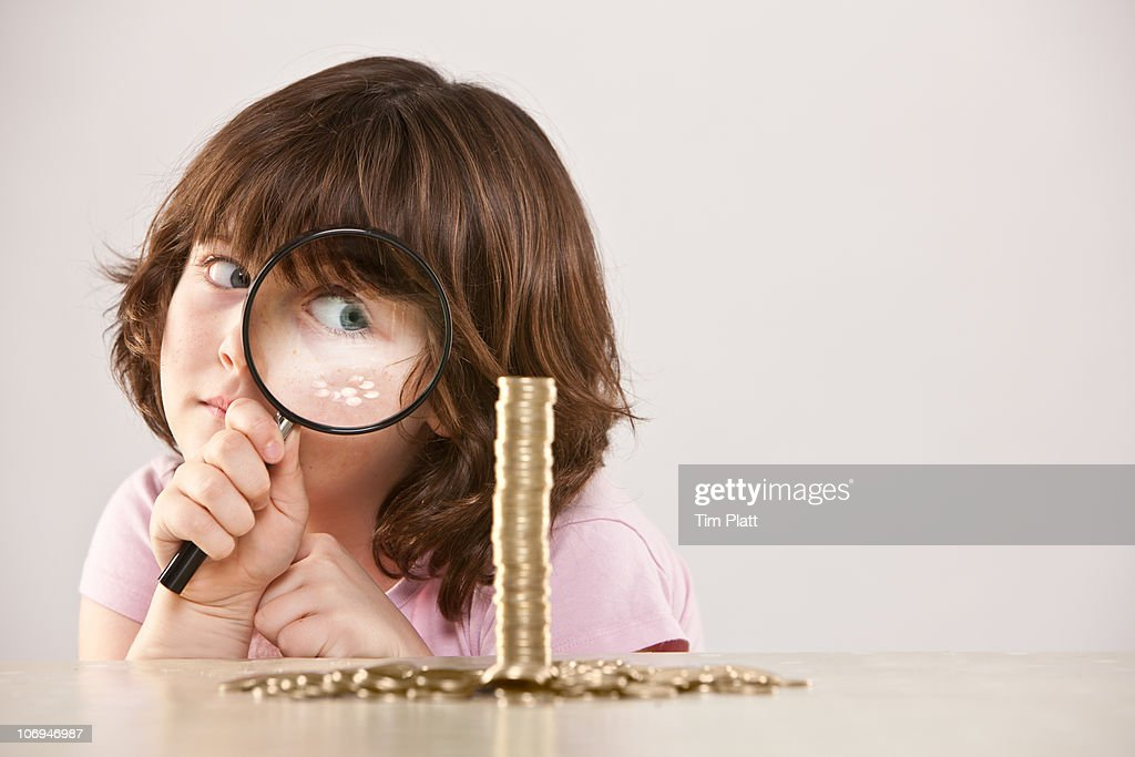 Young girl with magnifying glass and pile of coins : Stock Photo