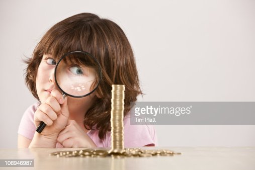 Young girl with magnifying glass and pile of coins : Foto de stock