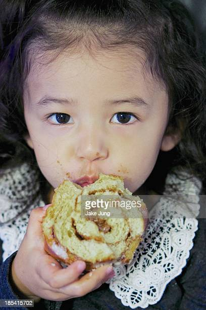 Young girl with messy face eating cinnamon roll