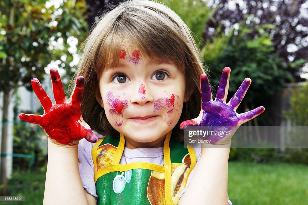 Young girl with painted hands and face : Stock Photo