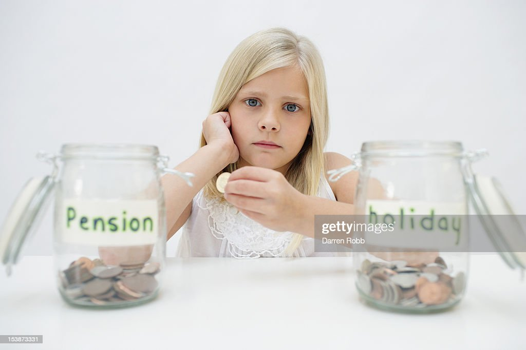 Young girl with pension and holiday savings jars : Stock Photo