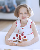 Young girl with plate of cupcakes