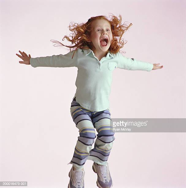 Young girl (4-6) with red hair jumping into air, mouth open