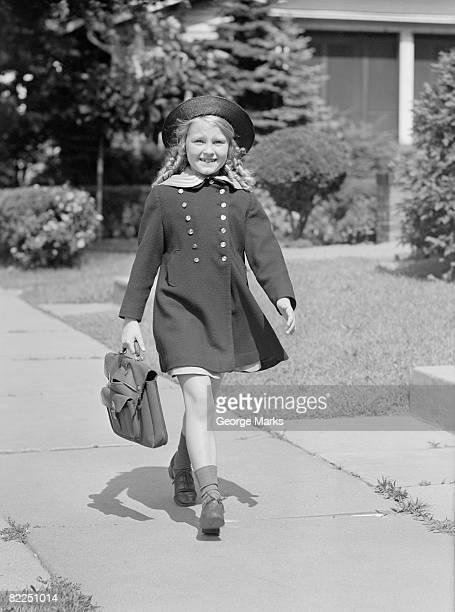 Young girl (8-9) with schoolbag on sidewalk, portrait