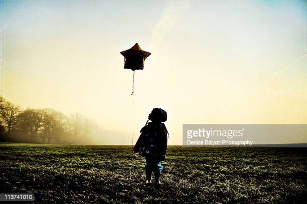 Young girl with star balloon on a foggy morning