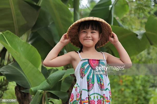 Young girl with straw hat working at the garden.