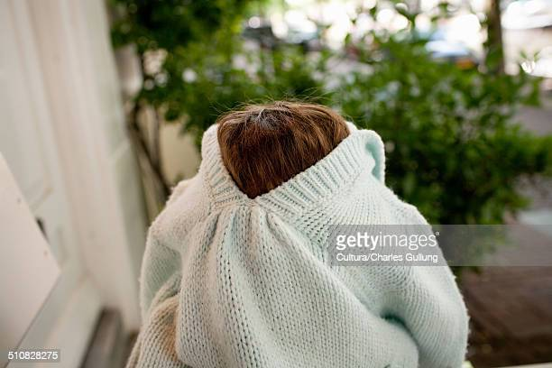 Young girl with sweater covering face
