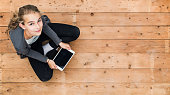 Top view of young girl teenager sitting on the floor and looking up. Using a tablet pc. Header mock up with copy space.