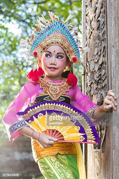 Young girl with traditional costume and fan in Bali temple