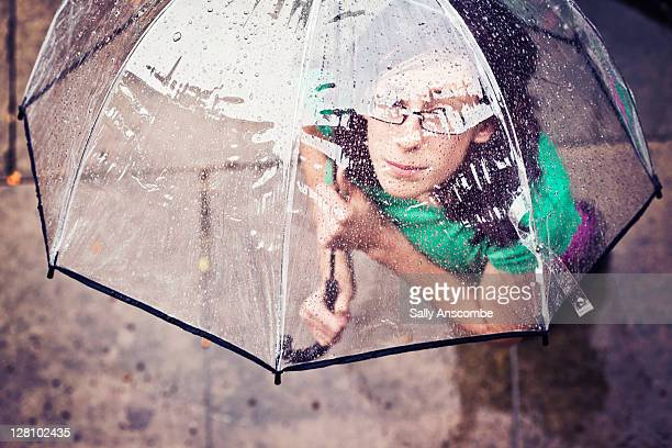 Young girl with umbrella in rain