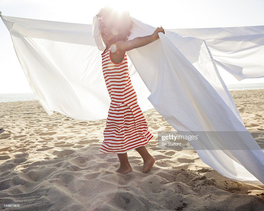 Young girl with white sheets at beach : Stock Photo