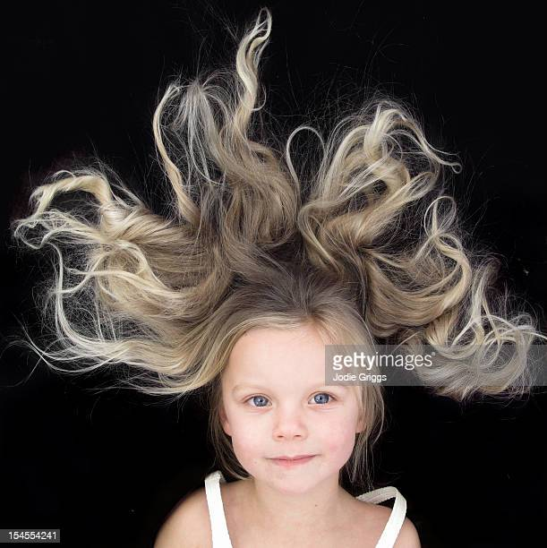 Young girl with wild hair against black background