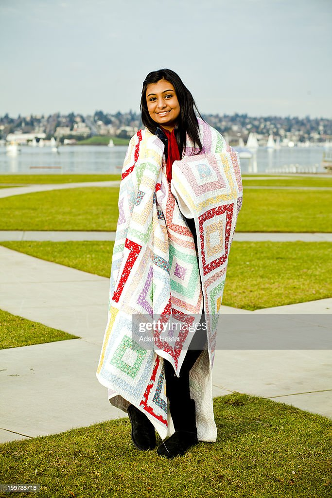 A young girl wrapped in a quilt outside. : Stock Photo