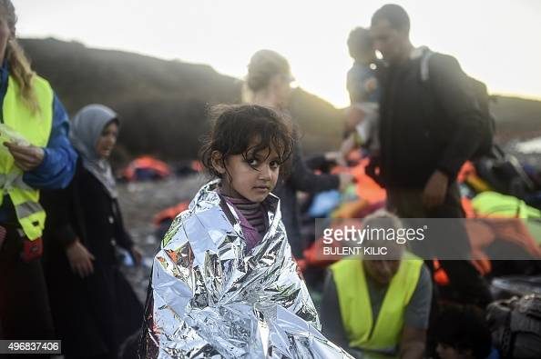 A young girl wrapped in an emergency blanket looks on after arriving with other refugees and migrants on the shores of the Greek island of Lesbos...