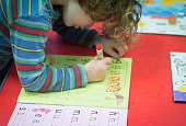 A young girl writes letters at a playgroup for preschool aged children in Chilcompton near Radstock on January 6 2015 in Somerset England Along with...