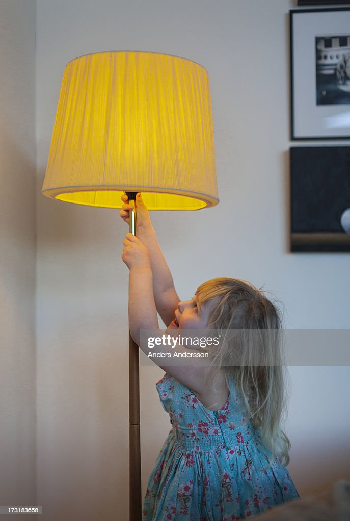 young girl/child w lit floor lamp : Stock Photo