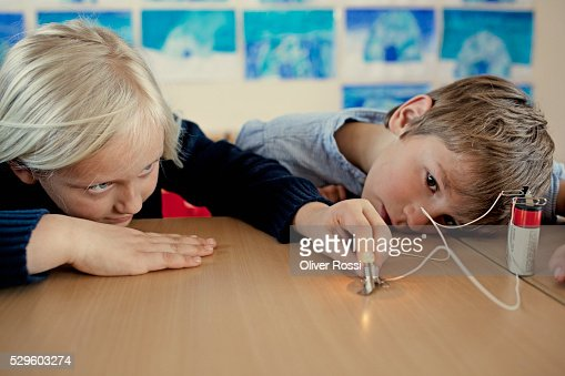Young girls (6--7) and boys (6-7) experimenting with electricity in science class : Stock Photo