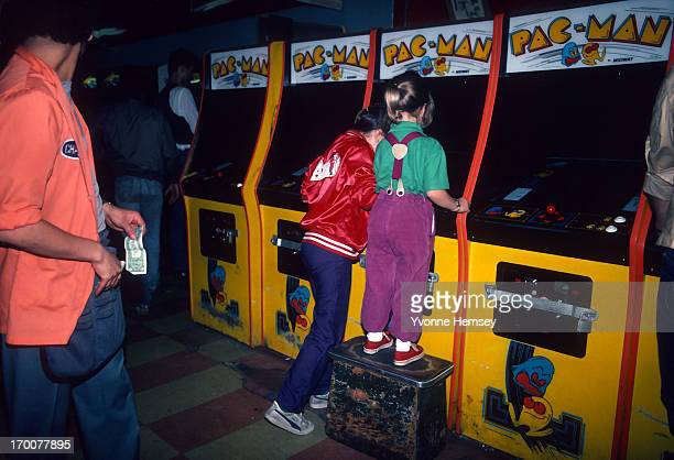 Young girls are photographed June 1 1982 playing PacMan at a video arcade in Times Square New York City