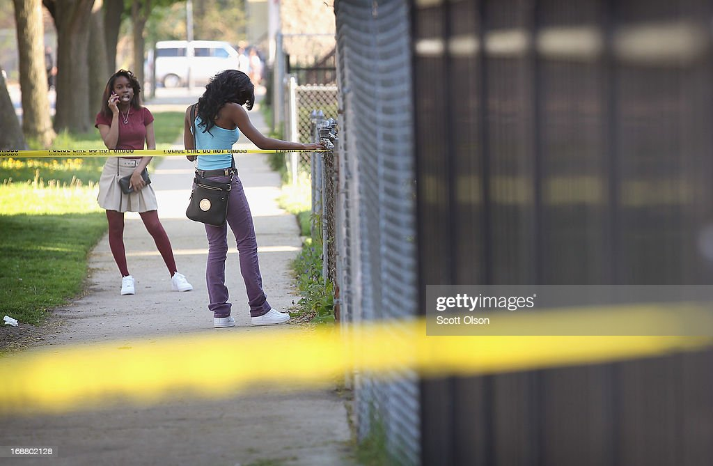 Young girls are stopped by crime scene tape as they try to visit a friend near the scene of a shooting where two men were wounded in the South Shore neighborhood on May 14, 2013 in Chicago, Illinois. The shooting was the first of several that left two men dead and 11 others wounded in the city between Monday afternoon and the early hours of Tuesday morning.
