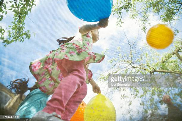 Young girls bouncing on garden trampoline with balloons