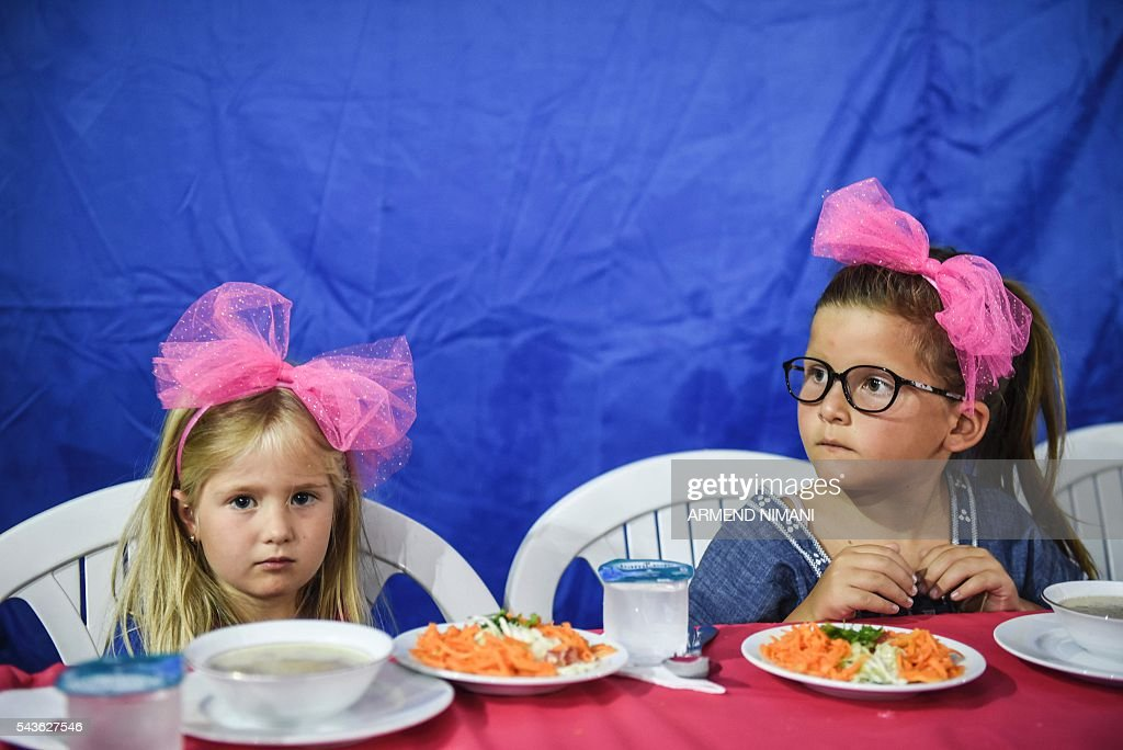 Young girls break the fast with a dinner distributed for free during the Muslim fasting month of Ramadan on June 29, 2016 in Pristina. Muslims fasting in the month of Ramadan must abstain from food, drink and sex from down to dusk, when they break the fast with meal known as iftar. / AFP / ARMEND