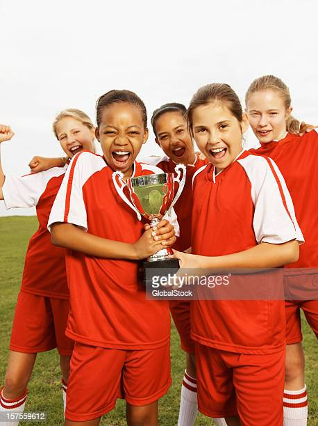 Young girls celebrating victory with a trophy