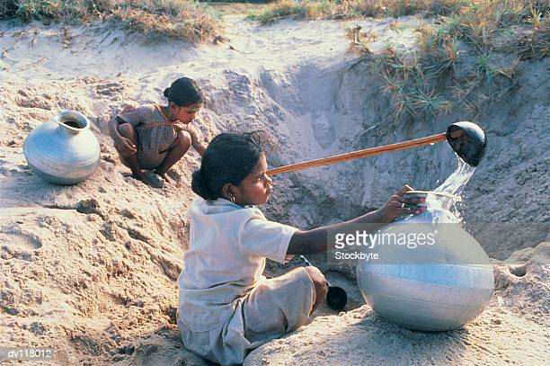 Young girls collecting water from holes dug in the ground,Udaipur,India