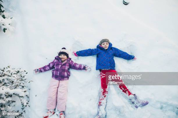 Young girls doing snow angel with big smiles in snow