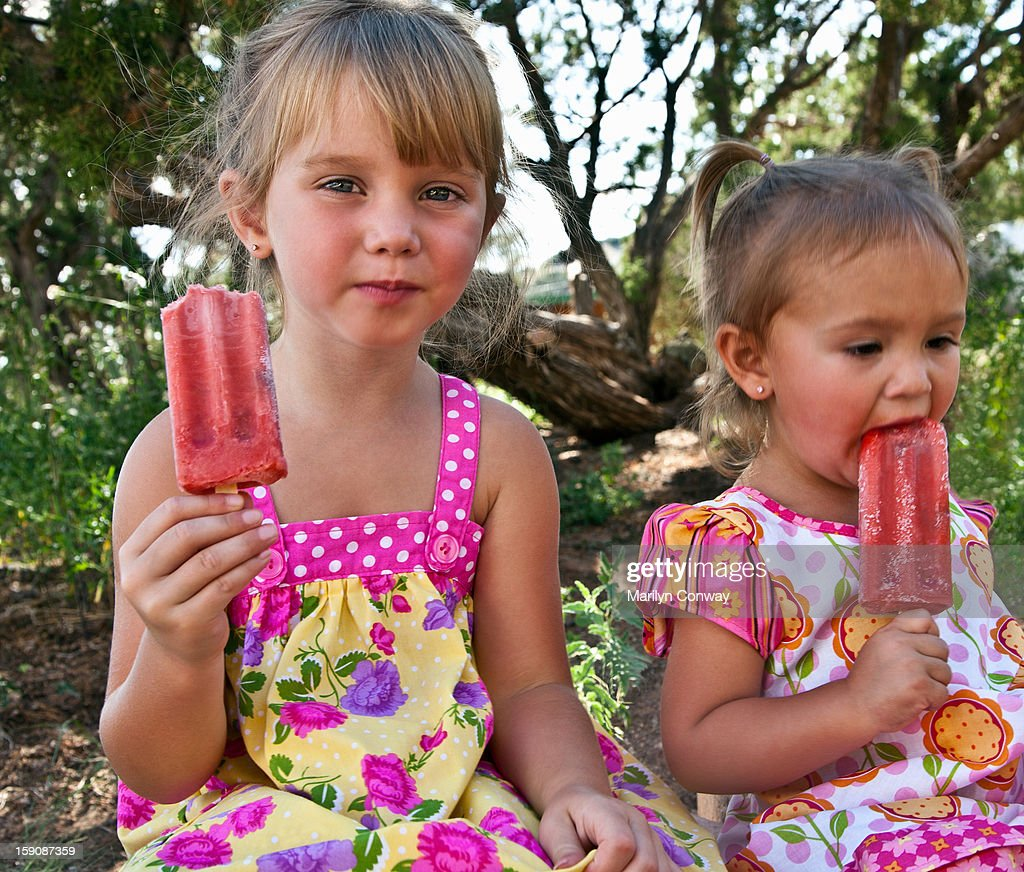 Young girls eating fruit popsicles outdoors : Stock Photo
