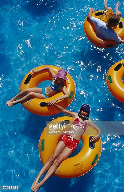 Young girls floating in rubber rings in swimming pool, Gold Coast, Australia