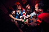 High angle of several young people, girls and one man, getting drunk at club party, sitting close together in dark red lit room and cheering to their meeting