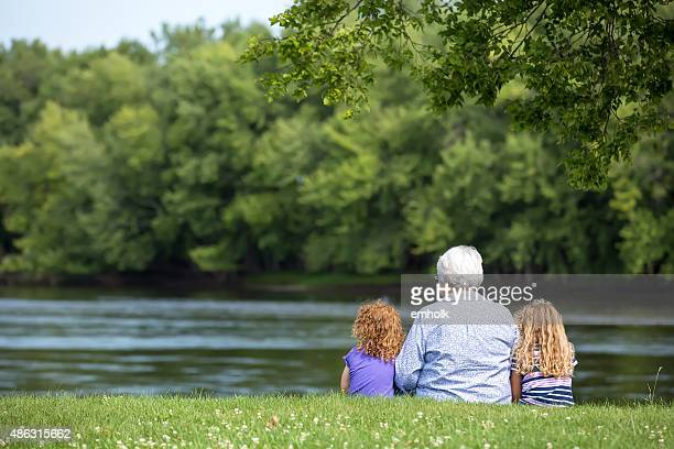 Young Girls & Grandma Sitting on Riverbank in Late Summer