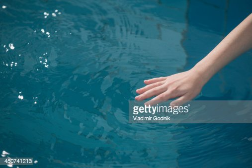 A young girl's hand rippling the water in a swimming pool