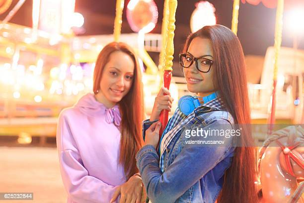 Young girls having fun on marry-go-round in amusement park